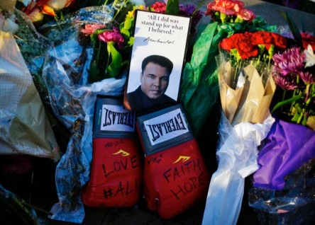 Boxing gloves and a message sit amongst flowers at a makeshift memorial to Muhammad Ali at the Muhammad Ali Center, Saturday, June 4, 2016, in Louisville, Ky. Muhammad Ali died Friday at age 74. (AP Photo/David Goldman)